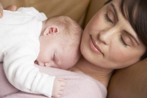 Portrait Of Mother Resting With Newborn Baby At Home